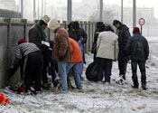 Immigrants waiting by a fence in Calais in 2008