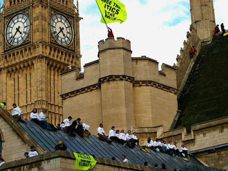 High on the agenda: The Greenpeace protesters fly their flag on the Houses of Parliament