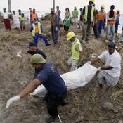Emergency workers carry a body found along Samoa's south east coast