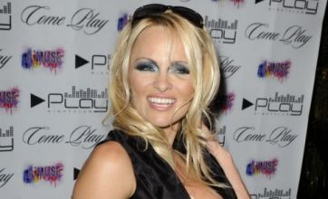 Pamela Anderson's plunging dress fails to contain her famous boobs