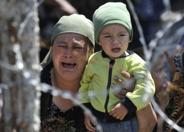 A tearful Uzbek woman and her child flee the city of Osh Picture: AP