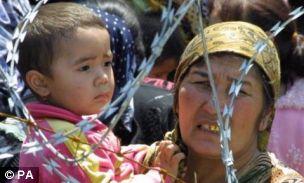 An ethnic Uzbek refugee holds a boy at a newly set-up refugee camp