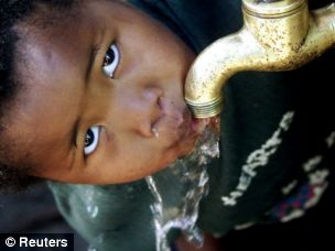 A child drinks from a communal tap providing clean water to a community near Cape Town, South Africa
