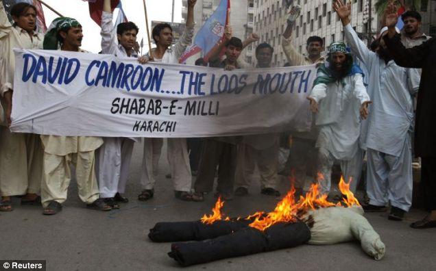 Protesters burn an effigy of Prime Minister David Cameron in Karachi, Pakistan