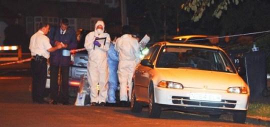 Police investigate the scene where exiled Pakistani politician Imran Farooq was stabbed to death