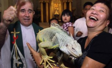 Priest blesses iguana as part of World Animal Day