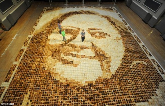 Slice to see you: Children take a closer look at the image of Mrs Whitfield, inset, made from 9,852 slices of toast Picture: Solent News