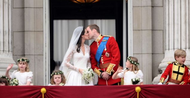 Prince William and Kate Middleton - the new Duke and Duchess of Cambridge - kiss on the balcony of Buckingham Palace. One bridesmaid looks enthusiastic about this, the other frankly appalled. (AFP/Getty)