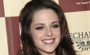 Kristen Stewart all smiles at premiere as Robert Pattinson films miles away