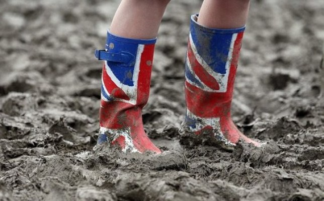 A woman makes her way across a muddy field in Union Jack Wellington boots on the third day of the Glastonbury Festival