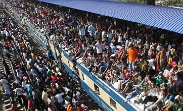 Rail passengers squeeze on to the roof of trains as Eid exodus begins