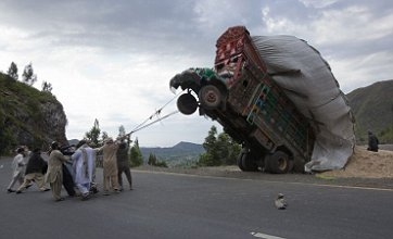 Men battle to right truck overloaded with wheat straw in Pakistan