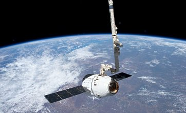 International Space Station grabs SpaceX Dragon cargo craft with robotic arm