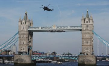Navy officers abseil from helicopter at Tower Bridge for Olympic rehearsal