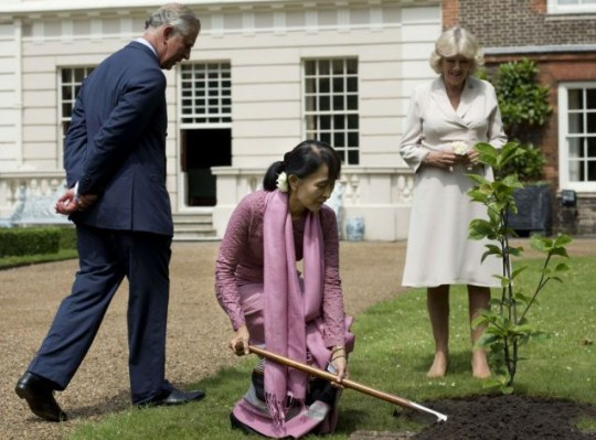 Myanmar democracy icon Aung San Suu Kyi (C) plants a tree as Britain's Prince Charles, Prince of Wales (L), and his wife Camilla, Duchess of Cornwall (R) look on at Clarence House in London, on June 21, 2012. Suu Kyi met British heir to the throne Prince Charles on June 21 ahead of her historic address to both houses of parliament. AFP PHOTO / POOL / BEN STANSALLBEN STANSALL/AFP/GettyImages