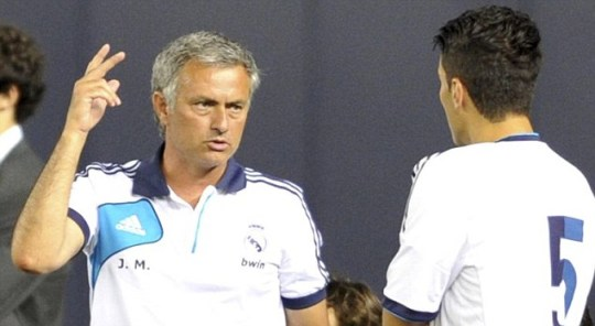 Real Madrid's manager Jose Mourinho (L) is seen on the sidelines talking to Nuri Sahin
