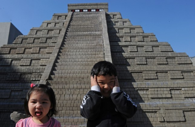 "Children gesture in front of a replica of a Mayan pyramid before a count-down ceremony organized by the National Museum of Natural Science to help ensure the public it is not the end of the world, in central Taichung on December 21, 2012. A digital ""doomsday clock"" on top of a two-storey replica Mayan pyramid erected at a museum in central Taiwan's Taichung city completed its countdown for the end of the world at 0600 GMT"