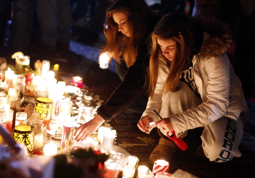 Visitors light candles at a memorial to the school shooting victims (Picture: AP)