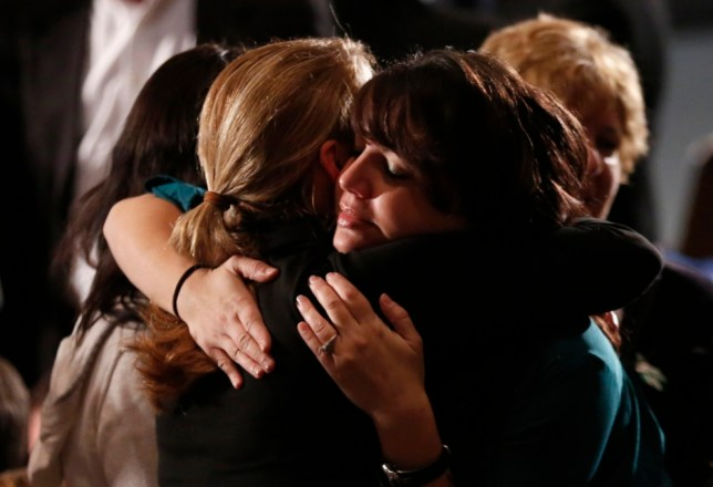 Mourners embrace during a vigil at Newtown High School (Picture: Reuters)