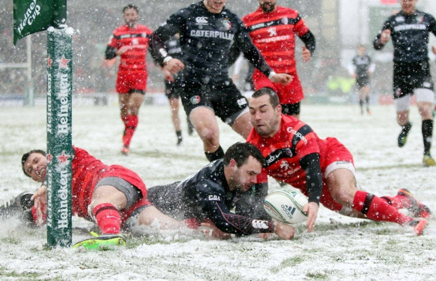 White out: Toulouse's Jean-Marc Doussain slides in at the corner to deny Leicester's Niall Morris a try at a wintry Welford Road (Picture: PA)