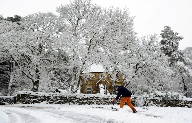 A man clears his path near Greenhaugh in Northumberland after heavy snow fall.