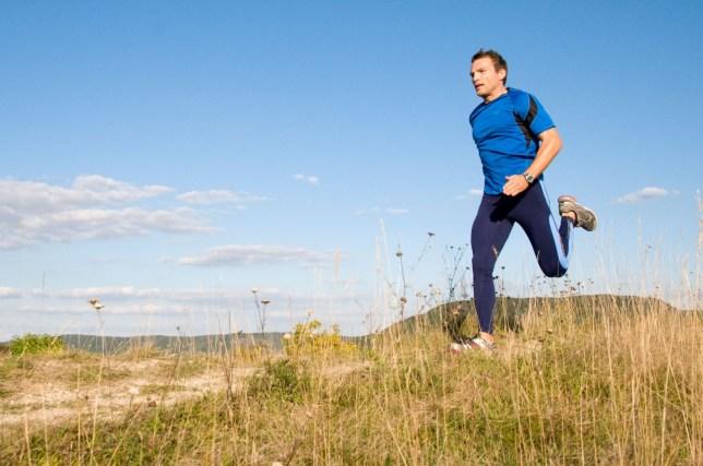 Man running over hill