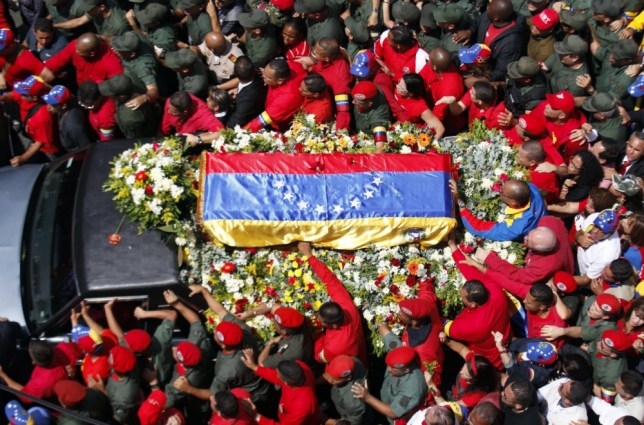 epa03612388 A vehicle carries the coffin with the remains of late Venezuelan President Hugo Chavez is accompanied by thousands of mourners during a parade through the streets of Caracas to the Military Academy, in Caracas, Venezuela, 06 March 2013. Venezuelan President Hugo Chavez died 05 March at a military hospital in Caracas. Chavez, 58, had been suffering from an unspecified form of abdominal cancer since June 2011 and was recovering from a fourth round of surgery in mid-December in Havana. He returned 18 February to Caracas. Chavez became gravely ill in recent days with a respiratory infection.  EPA/DAVID FERNANDEZ