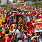 Supporters of Venezuela's late President Hugo Chavez carry portraits of him and independence hero Simon Bolivar as Chavez's coffin was driven through the streets of Caracas, March 6, 2013. Authorities have not yet said where Chaves will be buried after his state funeral on Friday. REUTERS/Carlos Garcia Rawlins (VENEZUELA  - Tags: POLITICS OBITUARY)