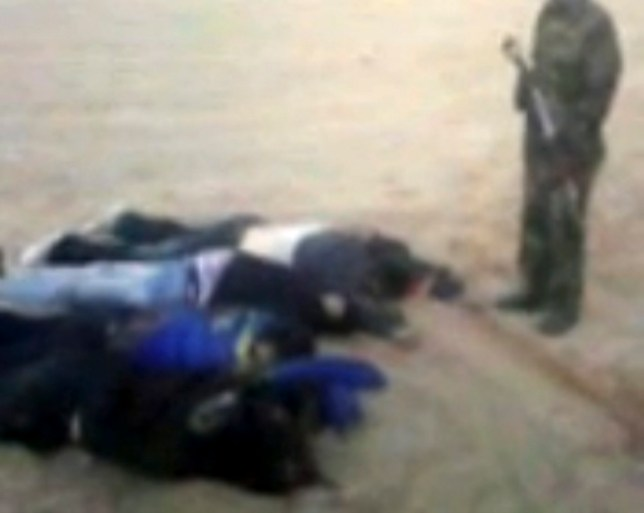 In this image from video posted on an islamist web site, an armed man appears to stand over the what are claimed to be the corpses of some of the seven foreign hostages abducted from northern Nigeria and later killed by Islamic extremists. European diplomats confirmed Sunday that the hostages from Greece, Italy, Lebanon and Britain had been killed after their abduction Feb. 16. Nigerian authorities have been silent about the killings. (AP Photo)