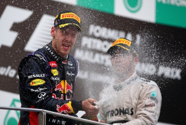 KUALA LUMPUR, MALAYSIA - MARCH 24:  Sebastian Vettel of Germany and Infiniti Red Bull Racing celebrates on the podium after winning the Malaysian Formula One Grand Prix at the Sepang Circuit on March 24, 2013 in Kuala Lumpur, Malaysia.  (Photo by Clive Mason/Getty Images)
