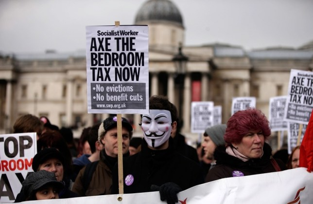 """Protestors hold signs and wear masks as they demonstrate against the proposed """"bedroom tax"""" gather in Trafalgar Square before marching to Downing Street on March 30, 2013 in London, England. Welfare groups are protesting the government's plans to cut benefits where families have surpassed the number of rooms they require. (Photo by Matthew Lloyd/Getty Images)"""