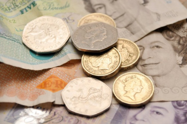 English coins on a backdrop of five, ten and twenty pound notes
