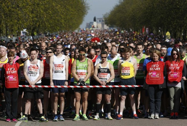 Runners stand in a silent tribute to the victims of the Boston marathon