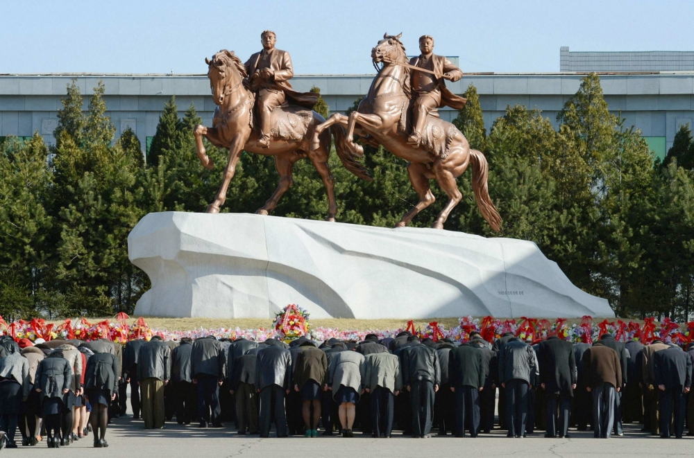 North Koreans bow to bronze statues of North Korea founder Kim Il-sung (L) and late leader Kim Jong-il at Mansudae in Pyongyang, in this photo taken by Kyodo April 14, 2013, a day before the birthday of the founder Kim Il-sung.  MANDATORY CREDIT.   REUTERS/Kyodo (NORTH KOREA - Tags: POLITICS) ATTENTION EDITORS - THIS IMAGE WAS PROVIDED BY A THIRD PARTY. FOR  EDITORIAL USE ONLY. NOT FOR SALE FOR MARKETING OR ADVERTISING CAMPAIGNS. THIS PICTURE IS DISTRIBUTED EXACTLY AS RECEIVED BY REUTERS, AS A SERVICE TO CLIENTS. MANDATORY CREDIT. JAPAN OUT. NO COMMERCIAL OR EDITORIAL SALES IN JAPAN. YES