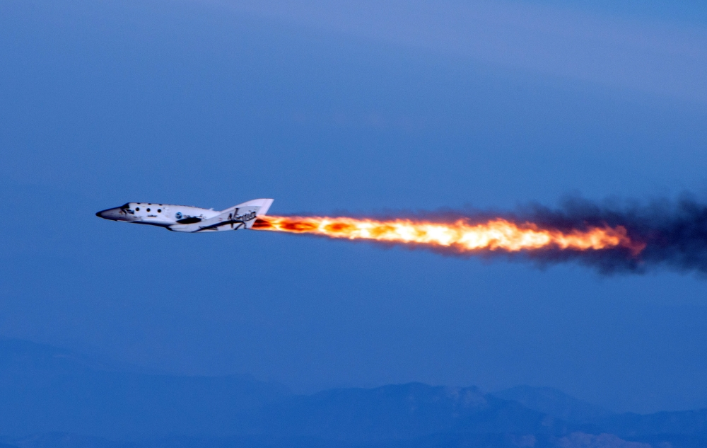 """This photo provided by Virgin Galactic shows Virgin Galactic's SpaceShipTwo under rocket power, its first ever since the program began in 2005. The spacecraft was dropped from its """"mothership,"""" WhiteKnightTwo, over Mojave, Calif., on Monday, April 29, 2013. The spaceship, bankrolled by British tycoon Sir Richard Branson, made its first powered flight in a test that moves Virgin Galactic toward its goal of flying into space later this year. While SpaceShipTwo did not break out of the atmosphere during the test flight, it marked a significant milestone for Virgin Galactic, which intends to take passengers on suborbital joyrides. (AP Photo/Virgin Galactic, Mark Greenberg)"""