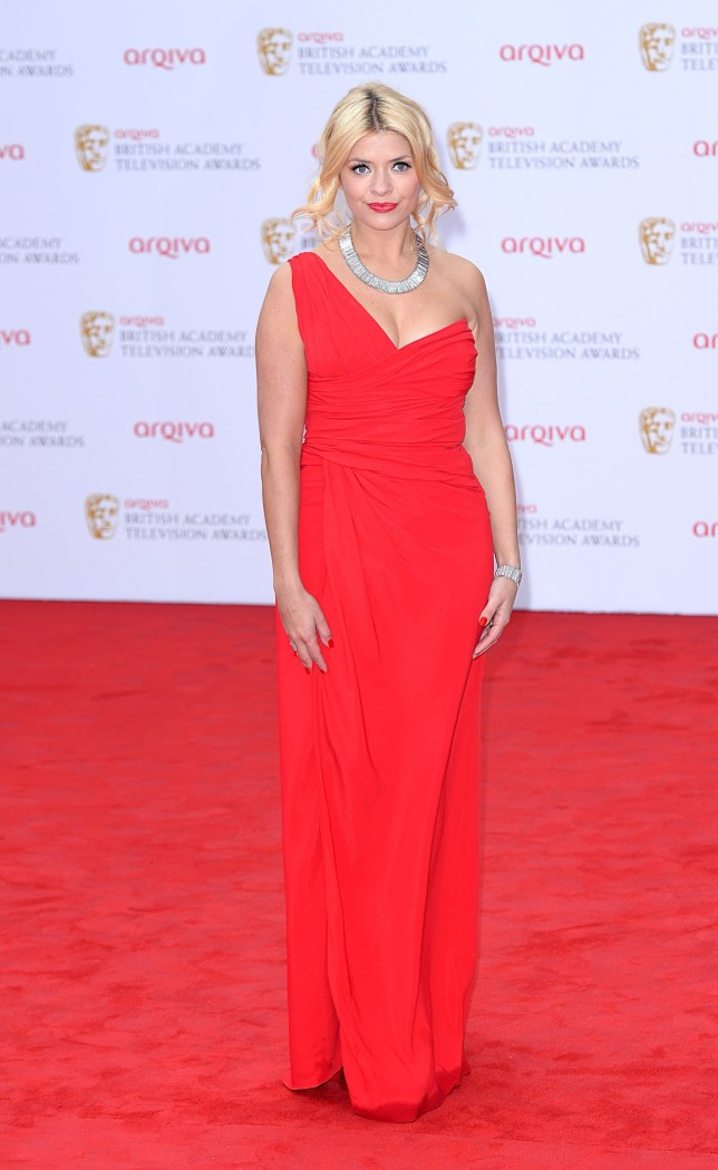 Lady in red: Holly Willoughby arrives at the Bafta TV Awards (Picture: PA)