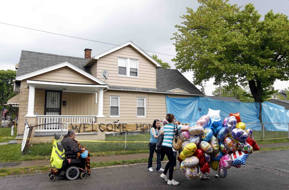 Deborah Knight (L), grandmother of Michelle Knight, makes her way down the street outside of kidnap victim Gina DeJesus' home in Cleveland, Ohio, May 10, 2013. Michelle Knight, freed earlier this week as the longest held of four captives in a dungeon-like Cleveland house, was discharged from the hospital on Friday, MetroHealth Medical Center said. It was unclear where Michelle, 32, was headed after she was released from the hospital. REUTERS/Matt Sullivan (UNITED STATES - Tags: CRIME LAW)