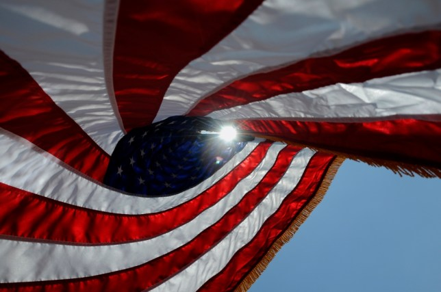 The sun shines through an American flag outside the Montgomery VA Medical Center of the Central Alabama Veterans Healthcare System in Montgomery, Ala., on Memorial Day, Monday, May 27, 2013. (AP Photo/The Montgomery Advertiser, Amanda Sowards)