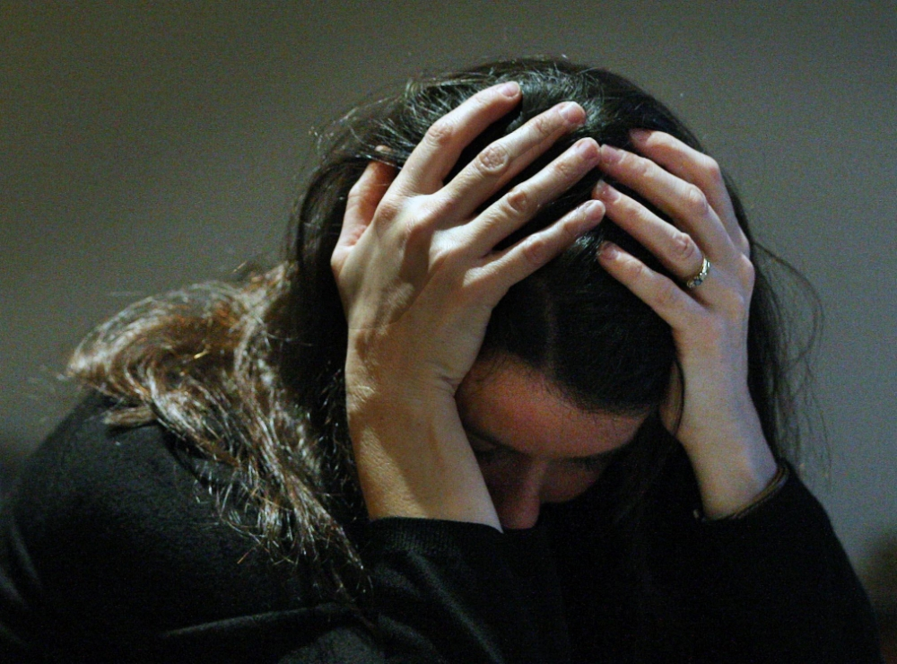 A woman holding her head in her hands as mental illness has become the drug industry's golden goose, a GP claimed as he cautioned against over-use of antidepressants.   PICTURE POSED BY MODEL. File photo dated 08/11/07. PRESS ASSOCIATION Photo. Picture date: Wednesday January 23, 2013. Des Spence said the medication was prescribed 'too easily' for too long and may have no benefit at all. And he argued that the current definition of clinical depression - two weeks of low mood, even after bereavement - was too loose and led to 'widespread medicalisation'. According to recent research, 75% of those who write such definitions have links with drug companies, he said. See PA story HEALTH Antidepressants. Photo credit should read: David Cheskin/PA Wire