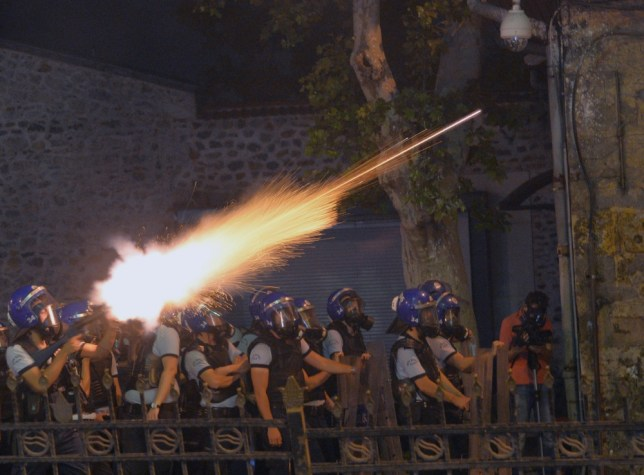 CORRECTS  DAY TO SATURDAY In this photo taken late Saturday, June 1, 2013, riot police fire, as they clash with protestors, near the former Ottoman palace, Dolmabahce, where Turkey's Prime Minister Recep Tayyip Erdogan maintains an office in Istanbul, Turkey. Protests in Istanbul, Ankara and several other Turkish cities appear to have subsided Sunday, after days of fierce clashes following a police crackdown on a peaceful gathering as protesters denounced what they see as Prime Minister Recep Tayyip Erdogan's increasingly authoritarian style. (AP Photo)