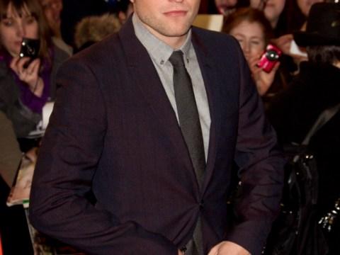 Robert Pattinson jets into Heathrow as he returns to London for Christmas