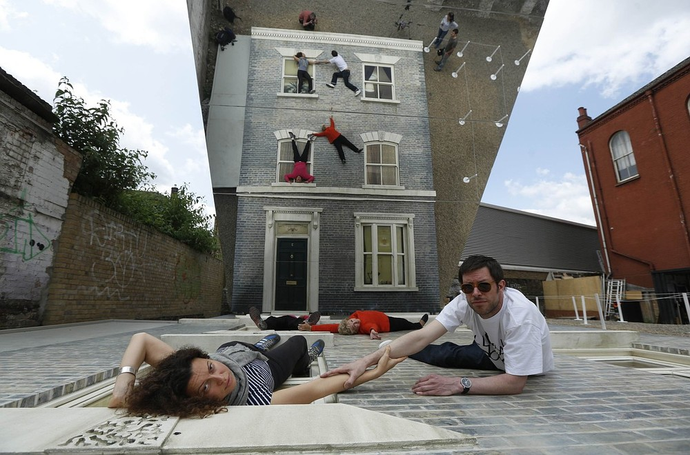 """Visitors JAKe and Emma Hayley pose on Argentine artist Leonardo Erlich's optical illusion installation """"Dalston House"""" in east London June 25, 2013. The artwork, commissioned by the Barbican Gallery, uses mirrors to create the impression of a house on which people can play and pose for visual effect. REUTERS"""