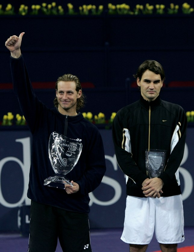 SHANGHAI - NOVEMBER 20:   David Nalbandian of Argentina holds the trophy as Roger Federer looks on after his five set victory against Roger Federer of Switzerland in the final at the Qi Zhong Stadium , November 20, 2005 in Shanghai, China. (Photo by Clive Brunskill/Getty Images)