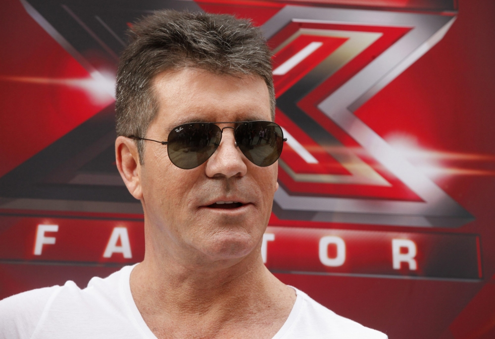"""Producer Simon Cowell and a judge for the upcoming season of the Fox television network reality series """"The X Factor"""", poses during a photo opportunity in Los Angeles July 11, 2013. REUTERS/Fred Prouser (UNITED STATES - Tags: ENTERTAINMENT)"""