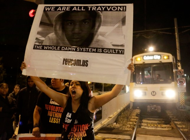 A protester blocks an Expo Line train at the intersection of Exposition and Crenshaw boulevards, following the George Zimmerman verdict in Los Angeles, California, July 13, 2013. A Florida jury acquitted Zimmerman on Saturday for the shooting death of unarmed black teenager Trayvon Martin, setting free a man who had become a polarizing figure in the national debate over racial profiling and self-defense laws. REUTERS/Jason Redmond   (UNITED STATES - Tags: CRIME LAW CIVIL UNREST TRANSPORT)