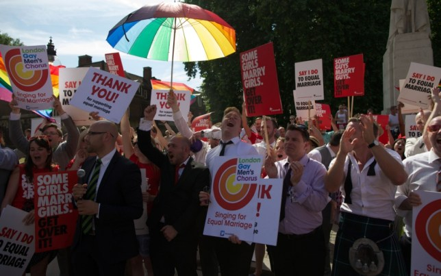 Gay campaigners rally outside the Houses of Parliament as the Marriage (Same Sex Couples) Bill gets an unopposed third reading by the Lords in central London on July 15, 2013. Gay marriage was set to be legalised in England and Wales after the controversial Bill introducing it cleared the Lords today. AFP PHOTO/ANDREW COWIEANDREW COWIE/AFP/Getty Images