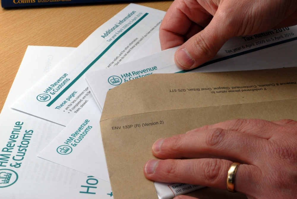 Completed Tax Return being dutifully put in an envelope to post back to HMRC Revenue and & Customs
