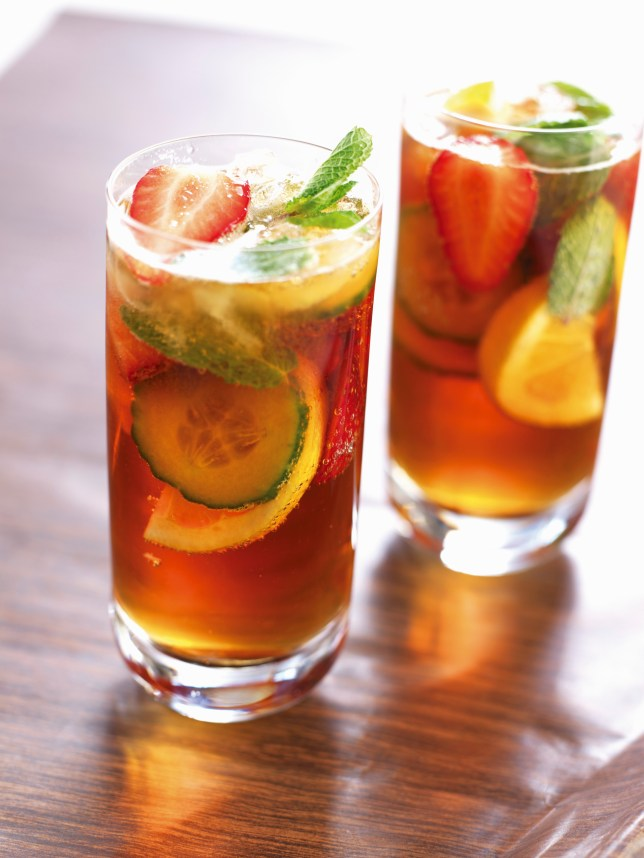 Two glasses of Pimm's cocktail with orange and mint --- Image by