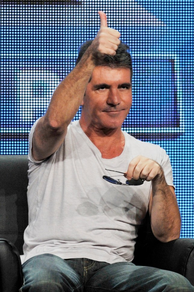 "Simon Cowell, a judge on the FOX series ""The X Factor,"" gives a thumbs-up to reporters following a panel discussion on the show at the FOX 2013 Summer TCA press tour at the Beverly Hilton Hotel on Thursday, Aug. 1, 2013, in Beverly Hills, Calif. (Photo by Chris Pizzello/Invision/AP)"