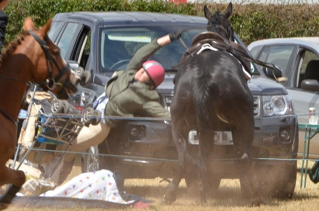 "PIC: APEX 05/08/2013 This is the terrifying moment a helpless tot came within inches of tragedy after a runaway horse - which bolted at a hunt meeting - miraculously just missed trampling as it lay on the ground. The dramatic scene was captured on camera as the giant animal threw its rider at the Minehead Harriers event at Dunster Castle, Somerset. Snapper Gilly Davidson witnessed the heart-in-mouth moment as the huge over excited horse went charging into the crowd at the annual event on July 24. She said: ""I could see there could be problems when the horse started to go. ""It bolted towards the perimeter where the spectators were and threw the rider off. ""She went over its head and onto the bonnet of a parked Land Rover. ""But then she fell off into a pram with a sleeping tot in next to the car. ""The child fell on to the floor while the horse was kicking and rearing just inches away from it. ""The hooves were just a matter of inches from it."" She added that there were no injuries to either the spectators, the rider or the horse. Although it's understood the owners of the Land Rover may be making a claim against the organisers for damage to the car. This picture shows the young child being knocked over whilst in its push-chair. ** SEE STORY BY APEX NEWS - 01392 823144 ** ---------------------------------------------------- APEX NEWS & PICTURES NEWS DESK: 01392 823144 PICTURE DESK: 01392 823145"